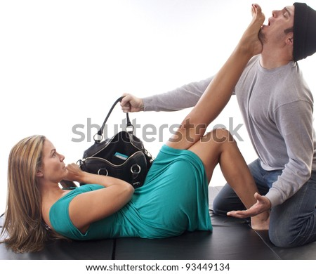 Woman in blue dress defending herself from a purse thief on black mat