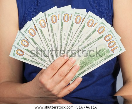 Woman in Blue Dress Holding New 100 US Dollar Bills
