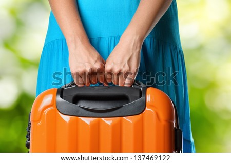 Woman in blue dress holds orange suitcase in hands on natural background.
