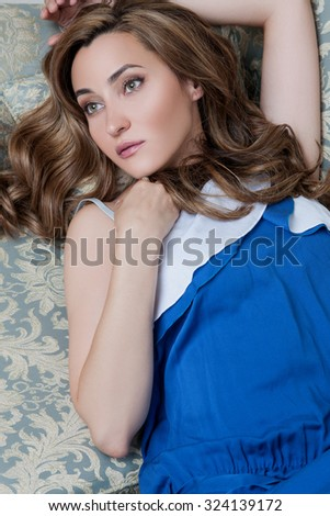 Woman in blue dress lying on a sofa in the interior, on her face beautiful make-up, her green big eyes looking at the camera. Beautiful girl lying on the back. portrait of a woman on the couch