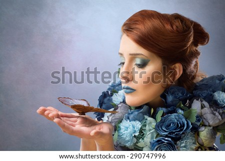 Woman in blue flowers with butterfly - stock photo
