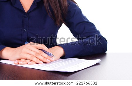 Woman in blue shirt signs a contract on a table, isolated over white - stock photo