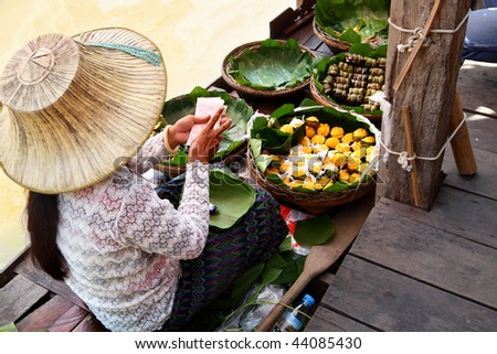 Woman in boat at Floating Market, Thailand - stock photo