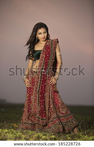 Woman in bright red lehenga choli on outdoor background. - stock photo