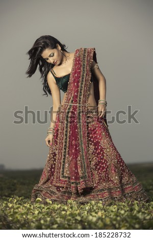 Woman in bright red lehenga choli on outdoor background.