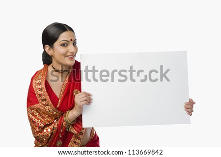 Woman in bright red mekhla holding a placard - stock photo