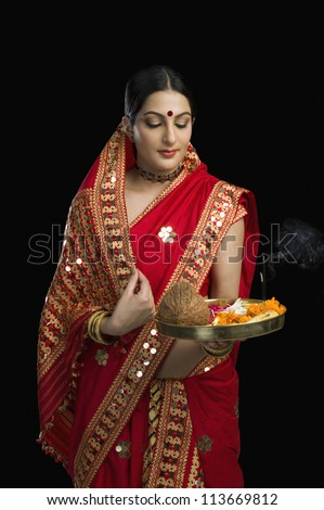 Woman in bright red mekhla holding religious offering