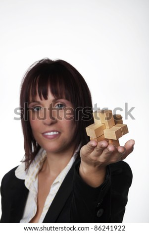 woman in business suit holding up a wooden 3D puzzle - stock photo