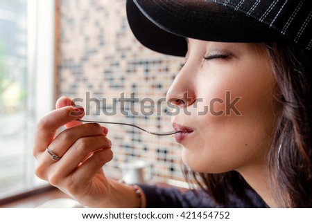 woman in cafe lick the spoon, delicious taste - stock photo