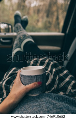 Woman in car with travel mug