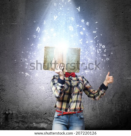 Woman in casual wear hiding her face behind book - stock photo