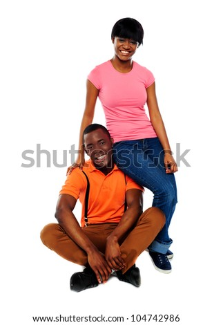 Woman in casuals sitting on mans shoulder. Happy african love couple