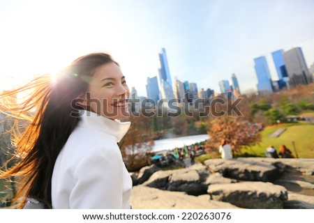 Woman in Central park, New York City in late fall early winter with skating rink in background. Candid smiling multi-ethnic girl on Manhattan, USA. - stock photo