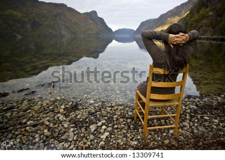 woman in chair near lake shores - stock photo