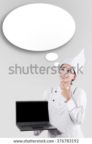 Woman in chef uniform thinking idea while holding a laptop computer - stock photo
