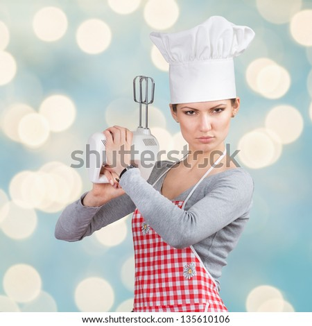 Woman in chief's hat �firing a gun� with the mixer on abstract blue background - stock photo