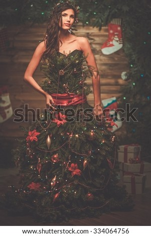 Woman in christmas tree dress in wooden interior  - stock photo