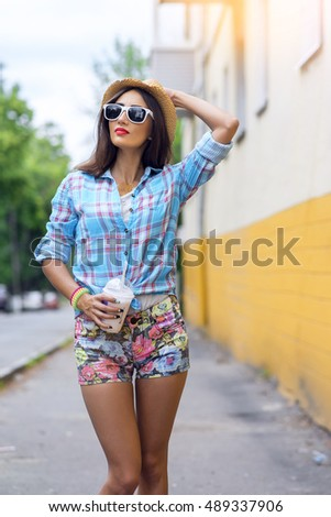 Woman in city on the background of a yellow wall, holding a milkshake, fresh juice in glasses, wearing a shirt with, makiyah sensual red lips, recreation concept lifestyle. Happy enjoying. straw hat