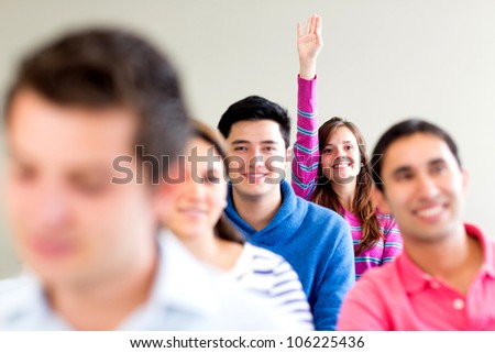 Woman in class raising her hand to participate - stock photo