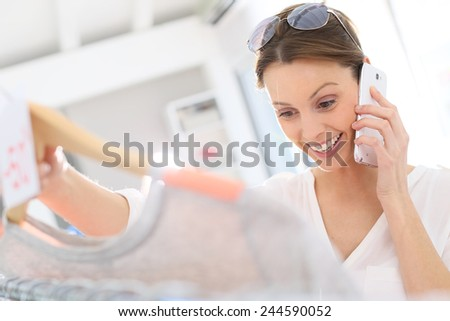Woman in clothing store talking to friend on phone - stock photo