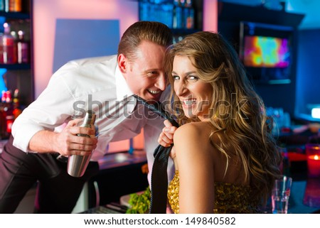 Woman in club dragging the barkeeper over the bar counter