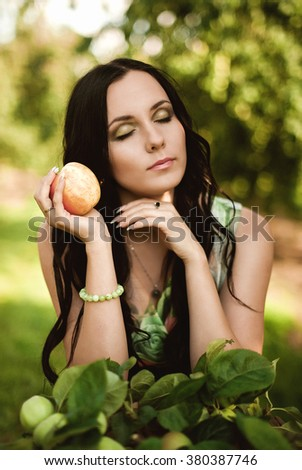 Woman in colorful maxi dress with box with apples in a sunny garden. Young smiling attractive woman is standing with full basket of organic apples in a sunlit orchard. Country happy lifestyle concept. - stock photo