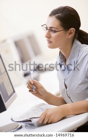 Woman in computer room circling items in a newspaper - stock photo