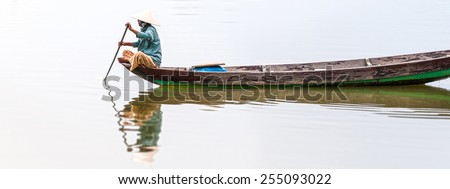 Woman in conical hat sitting on canoe and rowing. Traditional asian boat made of wood. Person holding paddle in hands. Ripple on water. Reflection of vessel in river. Travel by boat in Vietnam, Asia. - stock photo
