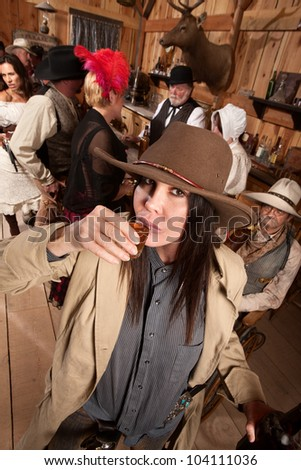 Woman in cowboy hat and bottle sipping whiskey at a bar - stock photo