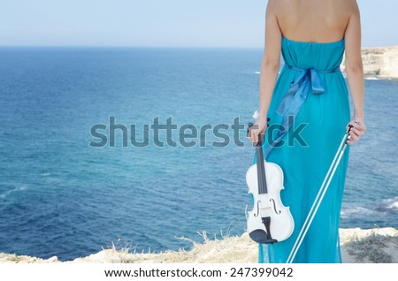 Woman in cyan dress holds violin and bow at sea shore - stock photo