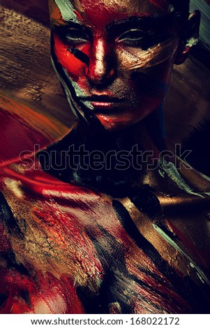 woman in dark colourful paint on skin - stock photo