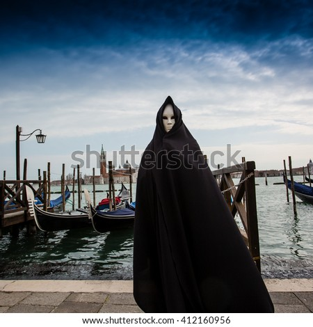 Woman in dark halloween like costume on streets of Venice during carnival