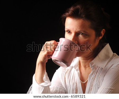 Woman in deep thought while drinking from a coffee mug - stock photo