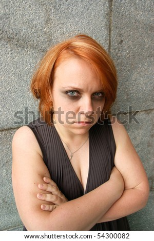 Woman in depression near old stone wall - stock photo