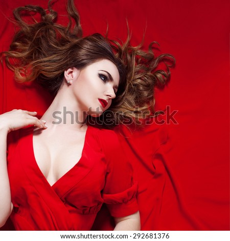 Woman in dress  lies on a red background,   looks right      - stock photo