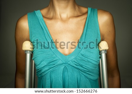 woman in dress with crutches - stock photo