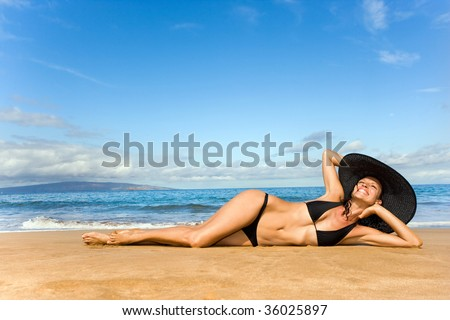 woman in elegant black bikini and wide brim hat on tropical maui beach in hawaii sunbathing and relaxing - stock photo