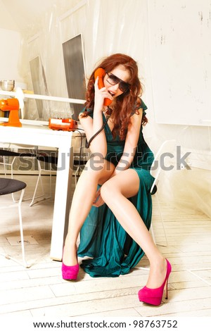 woman in elegant dress and high heels talk on retro phone indoor shot - stock photo
