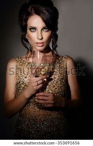 Woman in evening dress with glass of sparkling wine. - stock photo