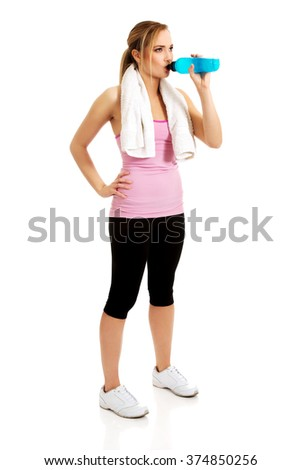 Woman in fitness clothes drinking isotonic drink. - stock photo