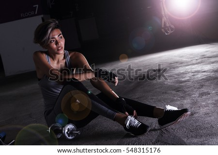 Woman in Fitness Suit do heavy exercise, training at crossfit Garage, dark shadow studio lighting, sit rest on floor look right, copy space for text logo