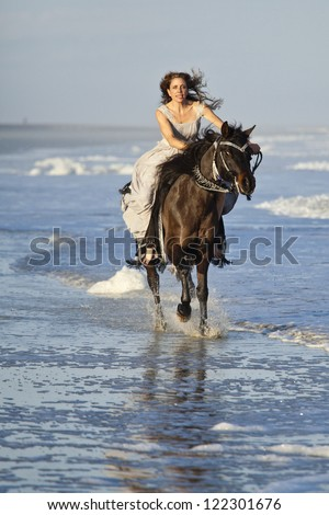 woman in formal dress riding galloping horse through surf - stock photo