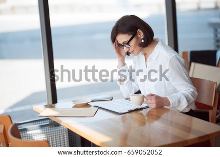 Woman in formal outfit sitting in cafe with coffee and working with documents.