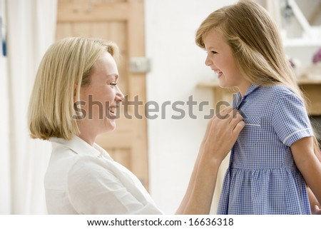 Woman in front hallway fixing young girl's dress and smiling - stock photo