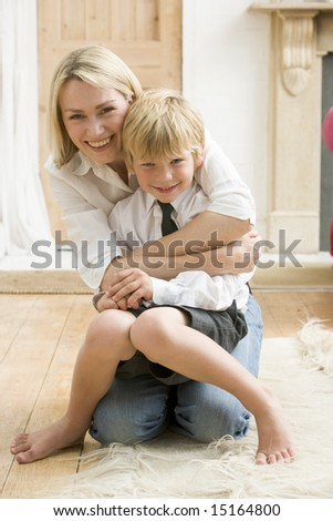 Woman in front hallway hugging young boy and smiling - stock photo