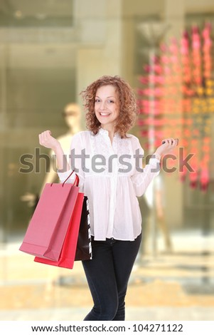 Woman in front of a shop Window with shopping bags - stock photo