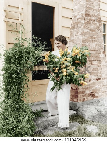 Woman in front of her house gathering flowers in her arms - stock photo