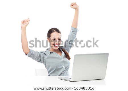 Woman in front of laptop with arms raised