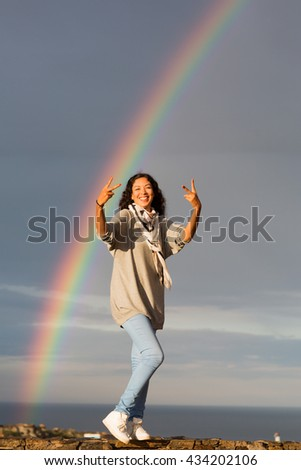 Woman in front of rainbow with peace sign - stock photo