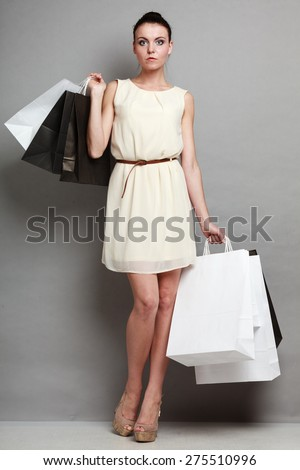 Woman in full length sale and retail concept. Girl with black and white shopping bags in hands on grey background in studio. - stock photo